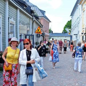Turister på en gata i Gamla stan i Borgå. Det är sommar och vackert väder.