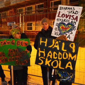 En kvinna och flera barn står utomhus och håller i skyltar. På skyltarna står det slagord som hjälp haddom skola.
