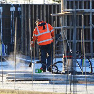 En byggarbetare i röd jacka jobbar på en byggarbetsplats. Han står med ryggen mot kameran och ser ut att hålla i en borste. Bakom honom finns en målfärgsburk och en dammsugare.