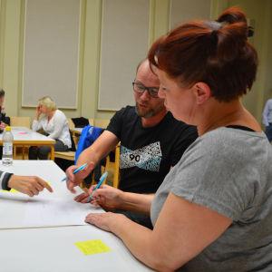 Flera personer sitter runt ett bord. De har ett papper framför sig och pekar på någonting som finns ritat på det.