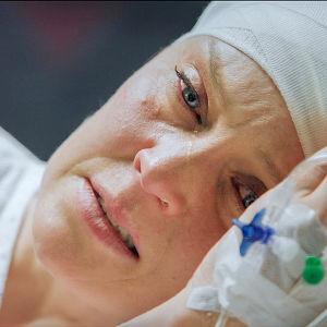 Sairaalasarjan näyttelijä makaa sairaalasängyssä ja itkee.