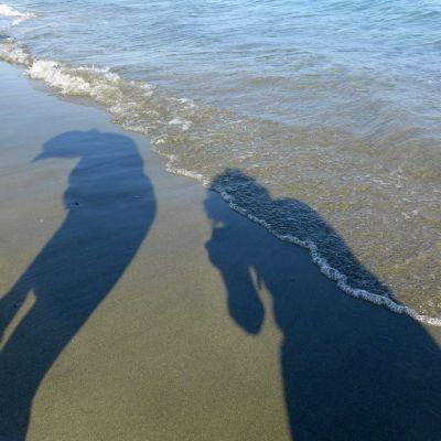 Ihmisten varjoja hiekalla, Välimenren laineet tulevat rantaan.