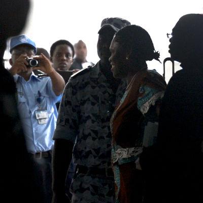 Simone Gbagbo eskorteras av polis till sin rättegång.