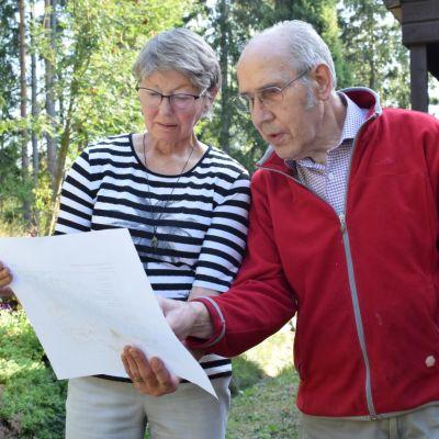 Ann-Marie och Hans Westerlund står med pappren över vindkraftsplanerna i handen på sin gårdsplan.