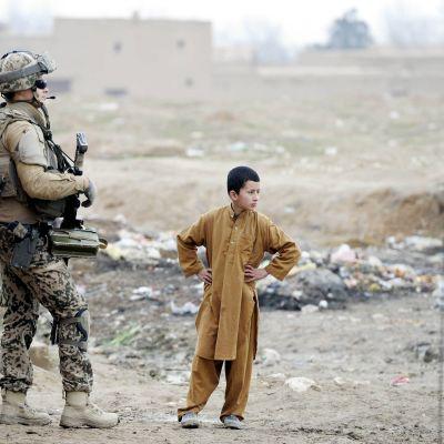 Suomalainen ISAF-kriisinhallintajoukkojen rauhanturvaaja jalkapartiossa tutustumassa tukikohta Camp Northern Lightsin lähiympäristön asukkaisiin Mazar-i-Sharifissa Afganistanissa tammikuussa 2013.