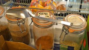 Stora glasburkar fyllda med kryddor står på en butikshylla.