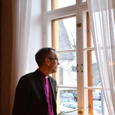 En medelålders man tittar ut genom ett fönster. Han har på sig en lila skjorta och en vit bricka runt halsen.