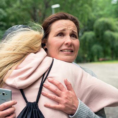 Pirjo Heikkilän esittämä Pirjo halaa Petra Aholan esittämää Mirjaa puistotiellä.
