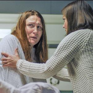 Sairaalasarjassa hoitaja pitelee pelokasta potilasta.