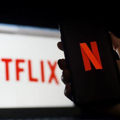 Suoratoistopalvelu Netflixin logo älypuhelimen ja tietokoneen näytöllä.