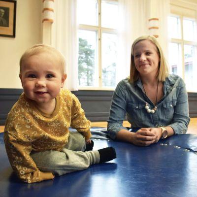 Ett leende barn sitter på en trampolin, en vuxen leende kvinna lutar sig mot trampolinen med ögonen på barnet.
