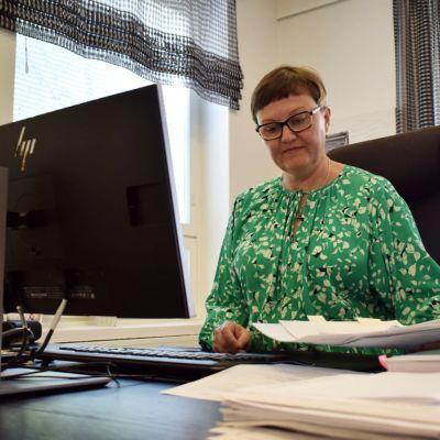 Anneli Pahta framför sin dator vid sitt skribord i kontoret.