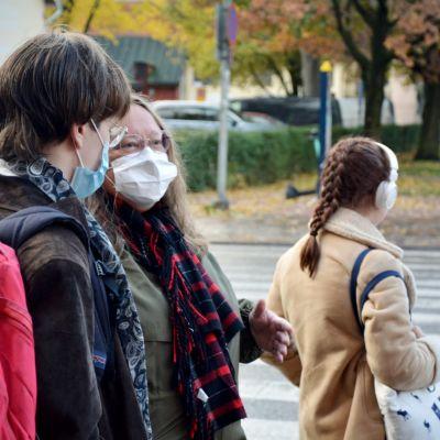 Två personer står och talar på gatan, båda har munskydd på sig.