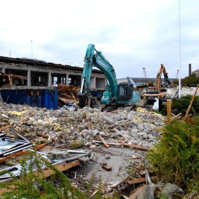 Två grävmaskiner i färd med att riva ett halvrivet ämbetshus.
