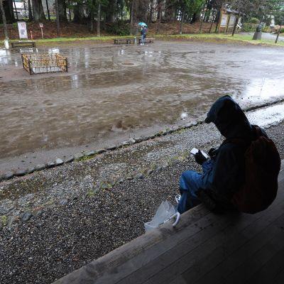 Mies istuu katoksessa kirjoittamassa.