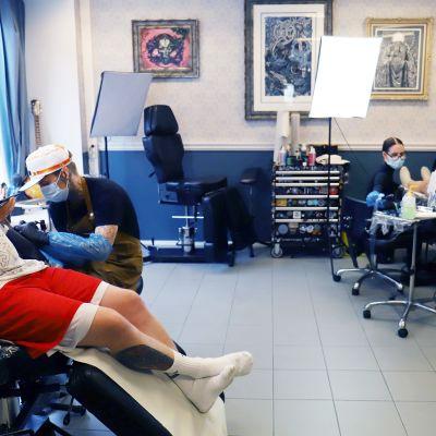 kaksi asiakasta tatuioitavana