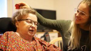 Pirkko Martikainen i blommig klänning tillsammans med sin personliga assistent.