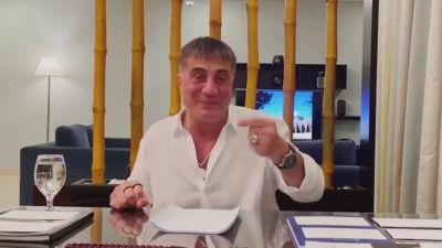 En man i vit skjorta talar med lyft hand.