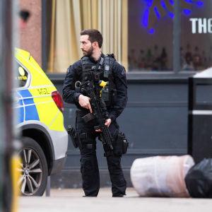 En polis med stort vapen står på en gata i Streatham, London, och ser mot vänster mot en polisbil.