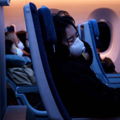 Hengityssuojin varustautuneita matkustajia lentokoneessa.