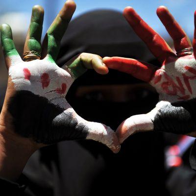 Mielenosoittaja jonka käsiin on maalattu Syyrian ja Jemenin liput.
