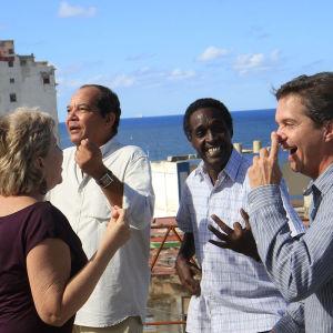 Fyra medelålders vänner dansar på en kubansk takterrass.