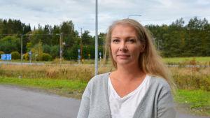 En blond kvinna står på en parkeringsplats. Bakom henne syns grönska och en väg.