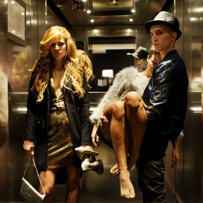 två unga mänskor i en hiss, den ena håller en död ung kvinna i famnen