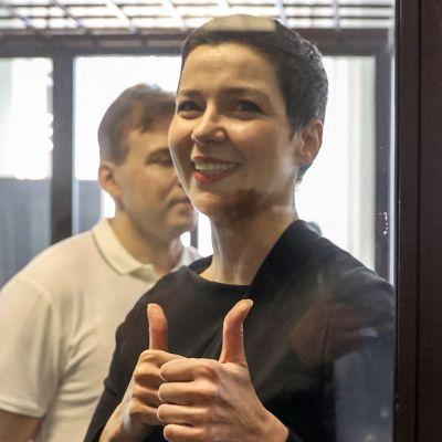 Miaria Kolesnikova visar tummen upp-tecken under rättegången mot henne. I bakgrunden står hennes medåtalade Maxim Znak.