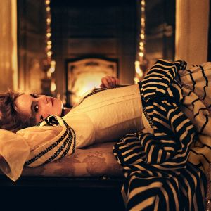 Emma Stones rollgestalt i The Favourite ligger i en utmanande ställning på en säng.