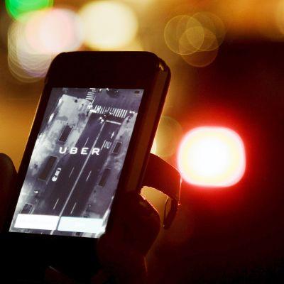 Uber-taksikyytisovelluksen käyttöä älypuhelimella.