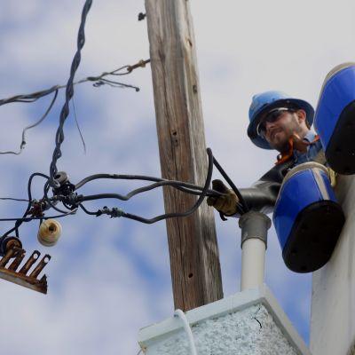 Mies korjaa sähkökaapeleita Puerto Ricossa.