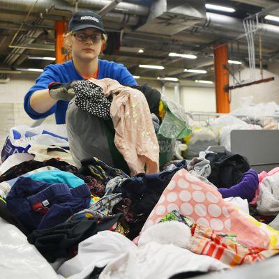 Nainen lajittelee vaatteita