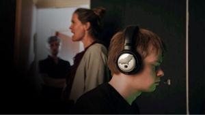 Sivukuvassa poika kuulokkeet päässä, nainen taustalla suu auki.