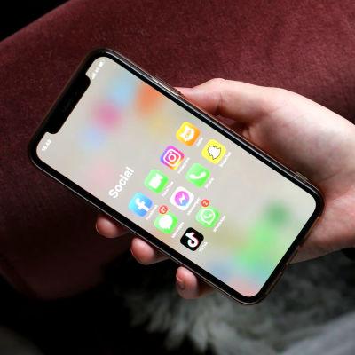"""Någon ligger ned i en fåtölj och visar sina telefon. På skärmen står """"social"""" och där finns personens sociala medier-appar."""