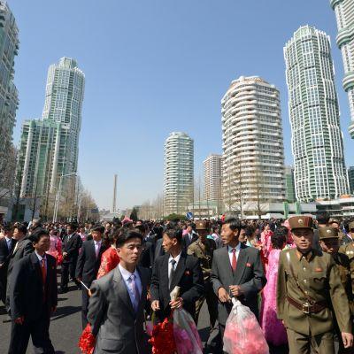 Ihmiset olivat pukeutuneet värikkäisiin mekkoihin ja univormuihin Pjongjangiin avatun uuden pilvenpiirtäjärykelmän avajaisissa.