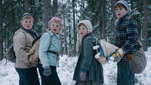 Fyra skrämda barn står i ett skogsbryn, vänder sig om i hast och tittar snett förbi kameran.