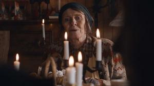 En äldre dam sitter bakom en klunga levande ljus vid ett julbord.