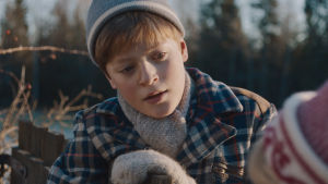 En ung pojke i vinterkläder sneglar ner mot ett annat barn.