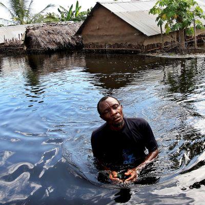 Mies kahlaa tulvavedessä.