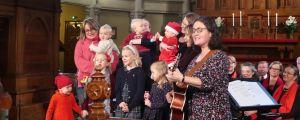 Musiklekgrupp med julklädda barn sjunger framme vid altaret i Johannes kyrka i Helsingfors. Delvis är de i mammors famn och leds av en kvinnlig gitarrist.