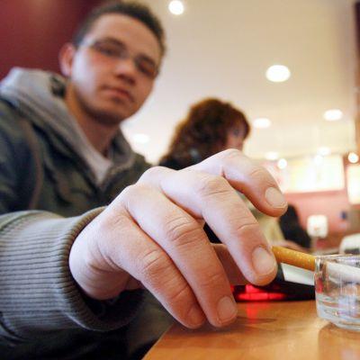 Mies tupakoi kahvilassa.