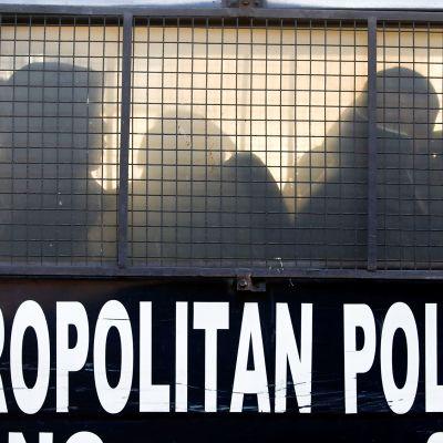 Pidätettyjä kiinalaisia miehiä poliisiautossa.