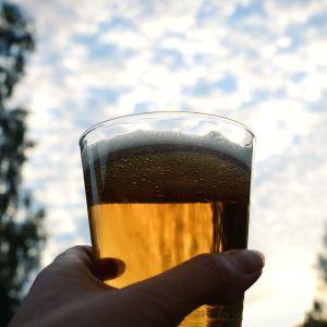 En hand håller ett ölglas upplyft mot himlen.