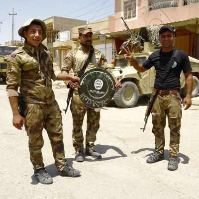 Irakin armeijan sotilaat esittelevät Isisin lippua valtaamassaan Shifaan kaupunginosassa Länsi-Mosulissa.