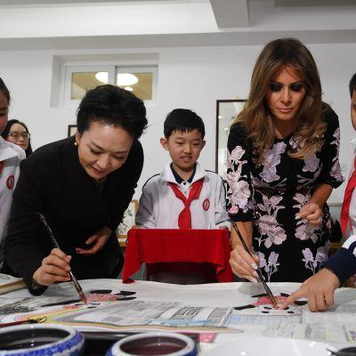 Peng ja Trump maalasivat silmät pandahahmoille vieraillessaan kalligrafiatunnilla Banchangin alakoulussa Pekingissä.