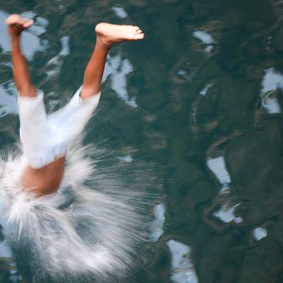Poika sukeltaa mereen pää edellä.