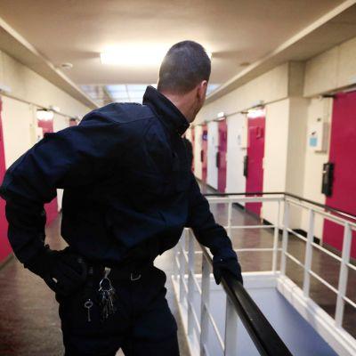 Vanginvartija seisoo vankilan käytävällä.