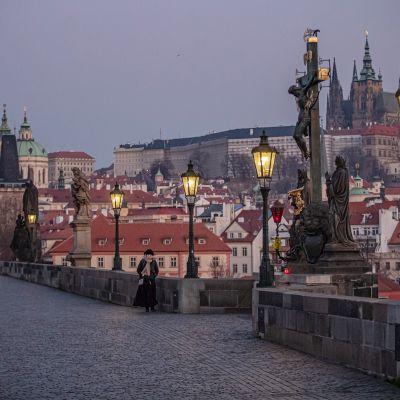 Nainen kävelee Kaarlen sillalla Prahassa.