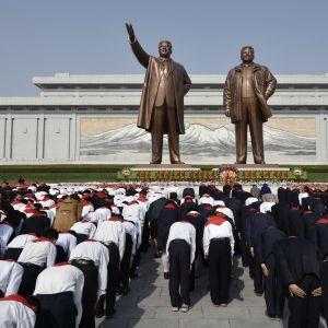 Vuonna 2016 julkaistussa kuvassa koululapset osoittavat kunnioitusta maan aikaisempia johtajiien kunniaksi pystytetyille näköispatsaille  Pjongjangissa.
